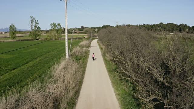 stockvideo's en b-roll-footage met drone standpunt van vrouwelijke runner training op dirt road - jogster