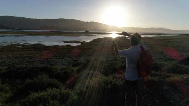 Drone point of view of young man framing nature