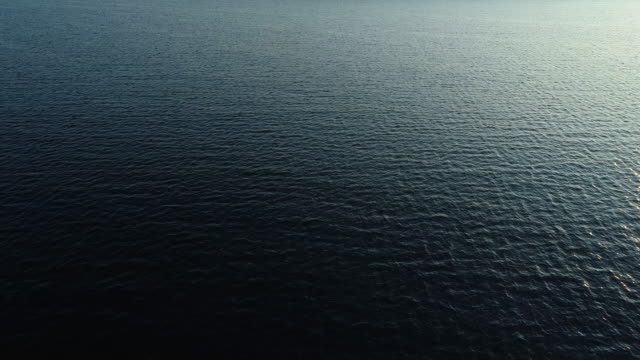 drone point of view on rippled sea water surface reflecting sunlight - b roll stock videos & royalty-free footage