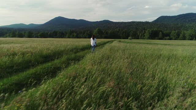 vídeos y material grabado en eventos de stock de drone point of view en young woman crossing a meadow - cruzar
