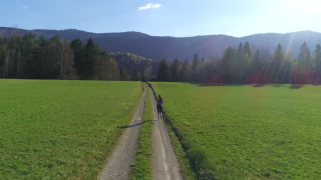 drone point of view on young woman jogging on country road - slovenia meadow stock videos & royalty-free footage