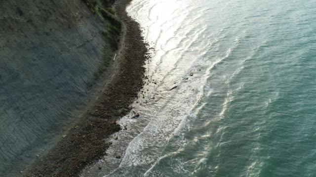 drohnen-sicht über einen felsigen kurzen strand mit steilen klippen - dramatischer himmel stock-videos und b-roll-filmmaterial