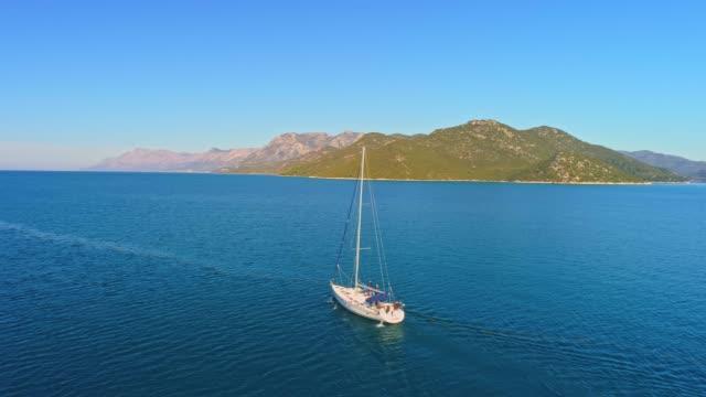 日当たりの良い、静かな青い海、リアルタイムで 4 k ドローンの視点ヨット - ブラック島点の映像素材/bロール