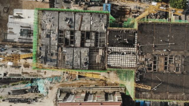 t/l pan drone point of view working in construction site - council flat stock videos & royalty-free footage