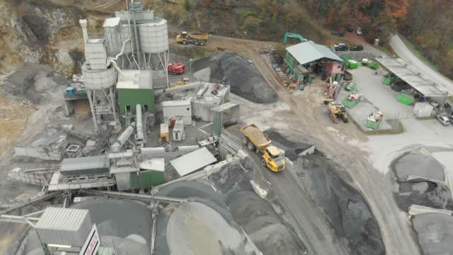 vídeos de stock e filmes b-roll de drone point of view - yellow dumper truck driving in reverse to unload gravel into a pit - veículo de construção