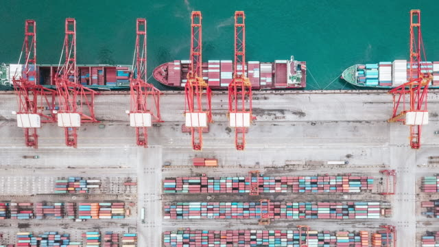 t/l pan drone point view of busy industrial port with containers ship - harbour stock videos & royalty-free footage