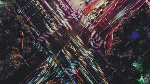 t/l ws ha drone point view of city street crossing at night - esposizione lunga video stock e b–roll
