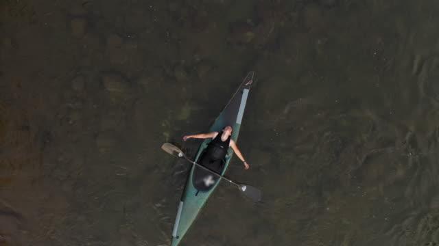 vidéos et rushes de vue d'intérêt de drone du kayakiste femelle flottant sur l'eau - kayak sport