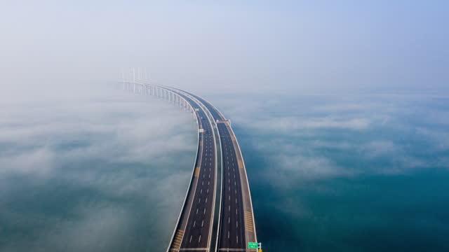 vídeos de stock e filmes b-roll de drone point view of jiaozhou bay bridge in the mist, qingdao city, shandong province, china - ponte suspensa