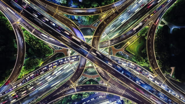 t/l drone point view of overpass and city traffic at night - la via giusta video stock e b–roll