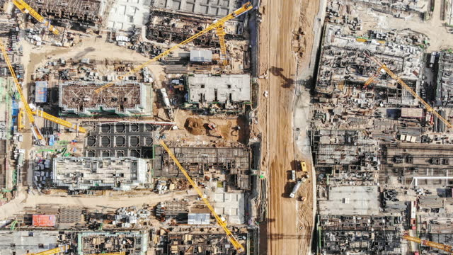 t/l pan drone point view of working construction site - scaffolding stock videos & royalty-free footage
