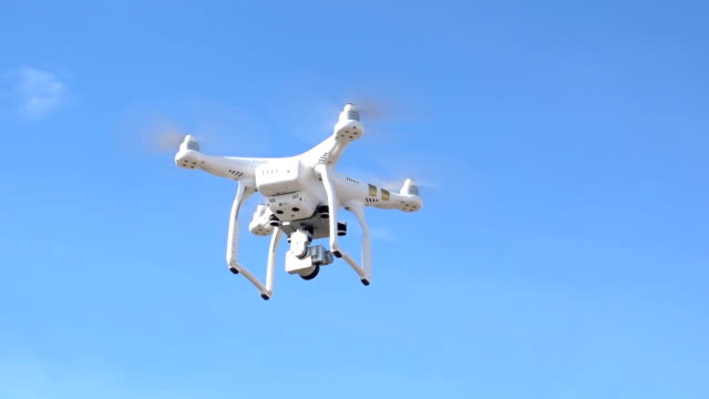 drone quad copter with digital camera flying hovering in the blue sky