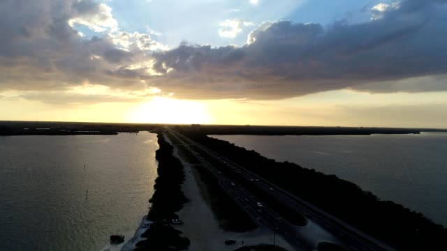 a drone raises above gandy bridge during sunset in tampa bay florida - tampa stock videos & royalty-free footage