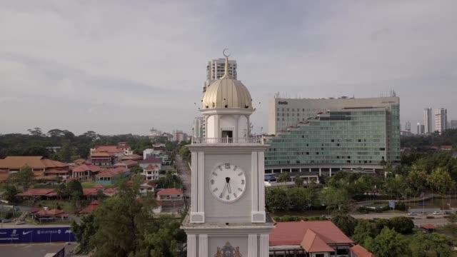 a drone reveals dataran bandaraya clocktower in johor bahru malaysia - turmuhr stock-videos und b-roll-filmmaterial