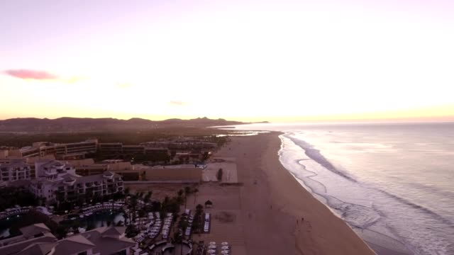 a drone reverses over a beach at sunrise in cabo san lucas baja california sur mexico - cabo san lucas stock videos and b-roll footage