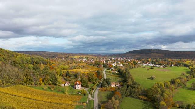 vidéos et rushes de a drone rises above a multi-colored valley in the vosges. - france