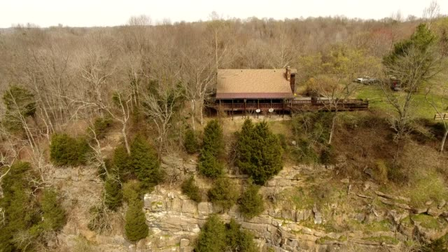 a drone rises and reveals a country home atop a cliff in ashland city tennessee - gebäudefries stock-videos und b-roll-filmmaterial