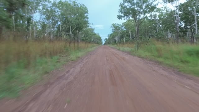 drone rises and tracks along dirt road near humpty doo, northern territory. as drone rises see scrubby bushland plain either side of road extending... - outback stock videos & royalty-free footage