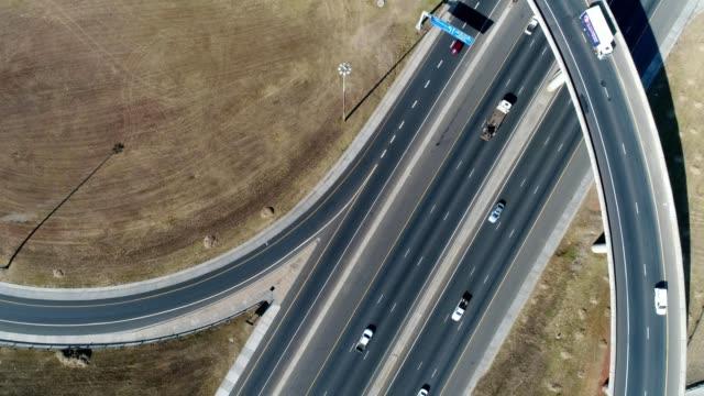 vídeos de stock e filmes b-roll de a drone rises birdseye over a highway intersection in johannesburg gauteng south africa - joanesburgo