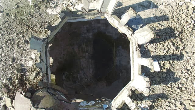 stockvideo's en b-roll-footage met drone rises from inside a war damaged building showing exposed rebar and twisted concrete columns on the roof. maarat al-numan is in idlib province. - materiaal