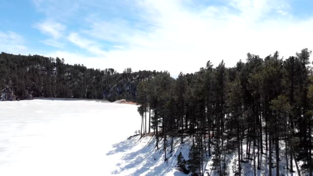 a drone rises out of a frozen center lake in custer south dakota - custer staatspark stock-videos und b-roll-filmmaterial