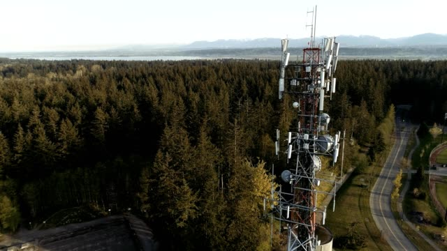 A drone rises over a radio tower reveals montains and forest in Surrey Canada
