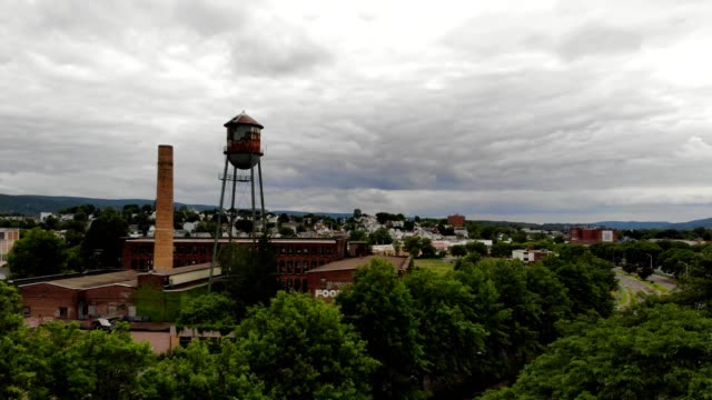 a drone rises over trees to view old murry's holding complex and smoke stack in wilkes-barre pennsylvania - wilkes barre stock videos & royalty-free footage
