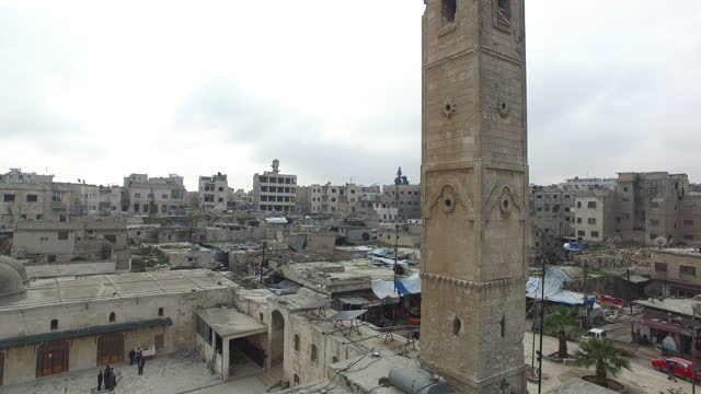 drone rising along the length of the minaret of the 12th century ayyubid-era mosque to reveal the town under an overcast sky. - circa 12th century stock videos & royalty-free footage