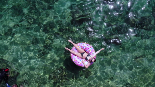 vídeos de stock e filmes b-roll de drone selfie of happy woman in inflatable donuts floating in the sea. - boia equipamento de desporto aquático