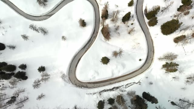 drone shoot - curvy winter road trough the mountains - steep stock videos & royalty-free footage