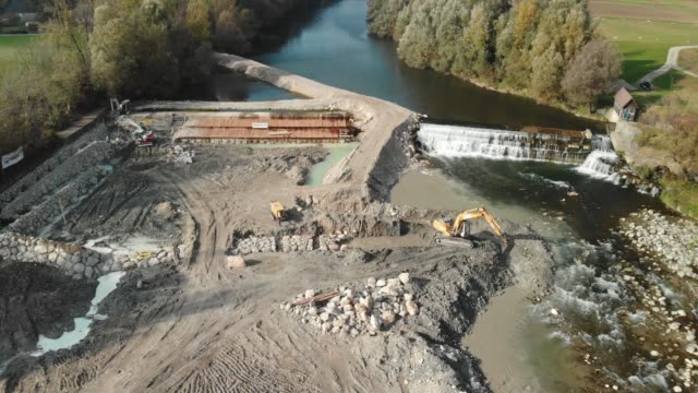 drone shoot of excavator digging up a pit for new dam on the river - crane construction machinery stock videos & royalty-free footage