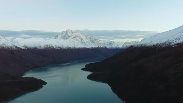 drone shoot of tranquil lake between mountains with a dense forest and snowy peaks (eklutna lake, alaska, usa) - anchorage alaska stock videos & royalty-free footage