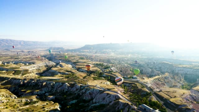 drone shoot panning 4k: aerial view of hot air balloons over cappadocia at sunrise,turkey - country geographic area stock videos & royalty-free footage