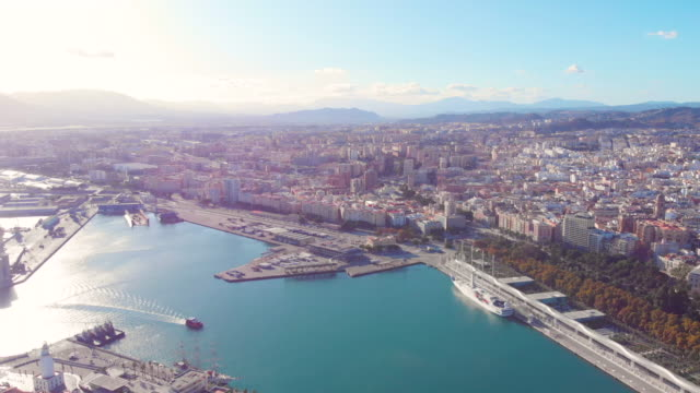 drone shot - 4k - aerial view of málaga harbor with a ship sailing - costa del sol with the beach and buildings in a sunny day - silvestre stock-videos und b-roll-filmmaterial