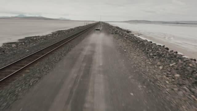 stockvideo's en b-roll-footage met drone shot above a truck driving into frame and then following it down a dirt road into the dust kicking up, utah, united states of america - grind