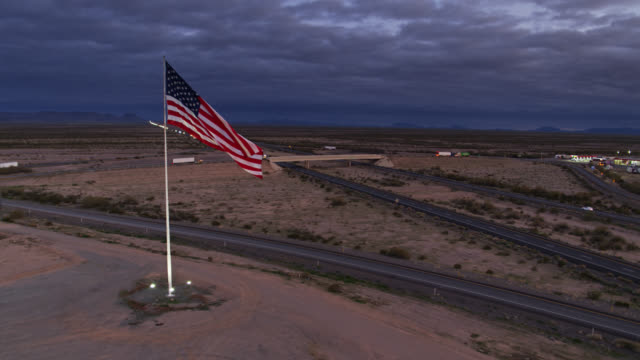 drone shot approaching massive us flag flying over truck stop - stars and stripes stock videos & royalty-free footage