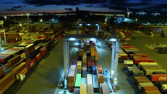 drone shot approaching straddle carrier moving containers in port at night - straddle carrier stock videos & royalty-free footage