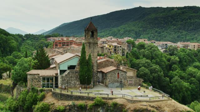 colpo drone in avvicinamento punto di vista e chiesa in cima alle scogliere, castellfollit de la roca - roca video stock e b–roll