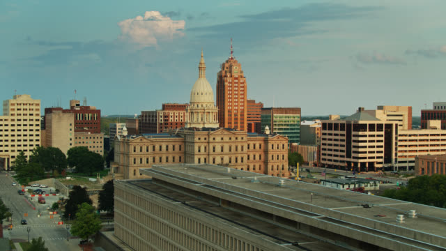drone shot ascending past the van wagoner building revealing michigan state capitol - lansing stock videos & royalty-free footage