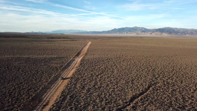 drone shot at sunrise of suv driving on empty gravel rural road in vast desert landscape with dust billowing off back of car and mountains in background.. - nevada stock videos & royalty-free footage