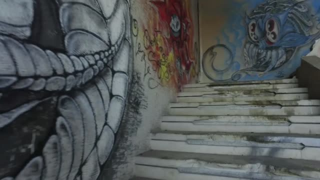 drone shot captures graffiti art on the wall beside the staircase of a squatted house - painted image stock videos & royalty-free footage