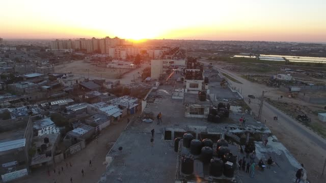 Drone shot captures people gathering together on the rooftops of abandoned buildings during sunset in Gaza Palestine