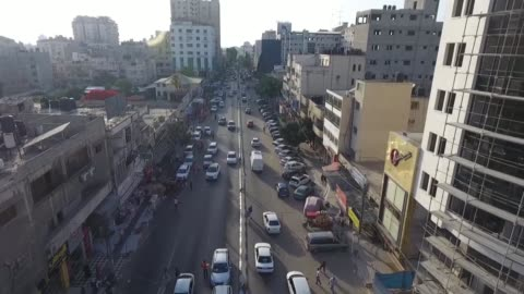 drone shot captures street traffic and buildings in gaza, palestine. the shot ends with a young traffic police directing the flow of traffic. - ガザ地区点の映像素材/bロール