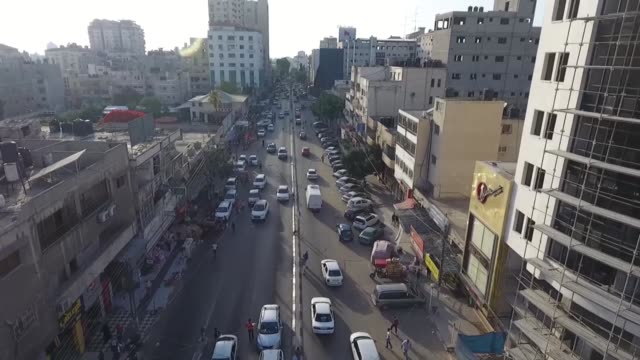 drone shot captures street traffic and buildings in gaza, palestine. the shot ends with a young traffic police directing the flow of traffic. - gaza strip stock videos & royalty-free footage