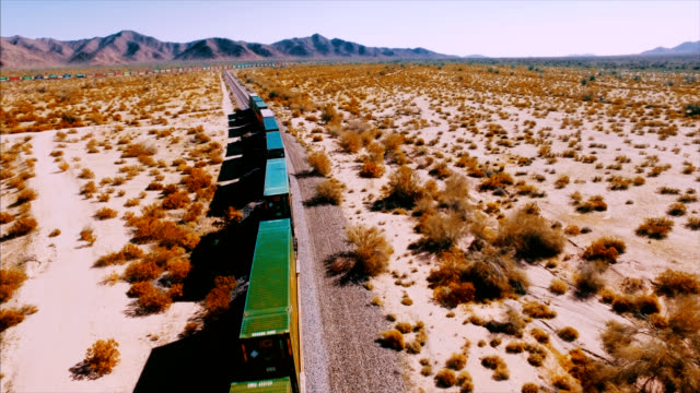 vídeos y material grabado en eventos de stock de drone disparó creando hermosa paralaje e imágenes como el tren pasa por debajo de la cámara. - tren de carga