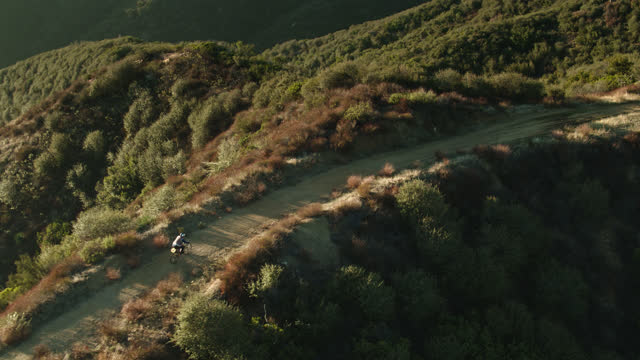 ダートトレイルでサイクリストに向かって降りるドローンショット - 国有林点の映像素材/bロール