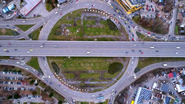 stockvideo's en b-roll-footage met drone schoot eagle eye luchtfoto time-lapse van stadsverkeer bij rotonde overdag - spitsperiode