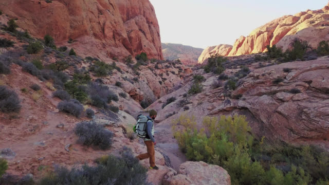 drone shot flies over lone backpacker as he walks to the edge of rocky outcrop to survey the moab landscape. - butte rocky outcrop stock videos & royalty-free footage