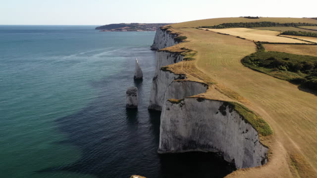 drone shot flying along chalk cliff coastline, dorset, england, united kingdom - rock face stock videos & royalty-free footage