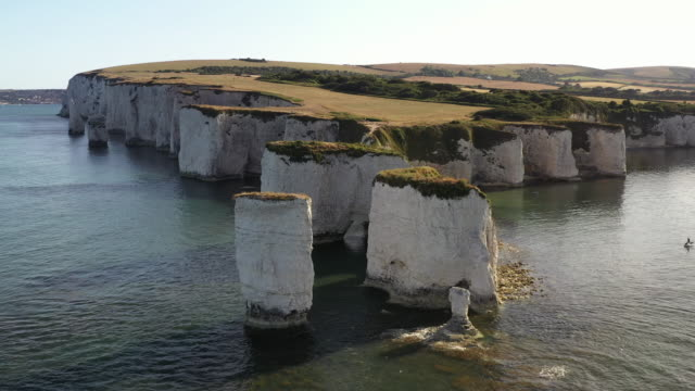 drone shot flying backwards from old harry rocks, dorset, england, united kingdom - rock face stock videos & royalty-free footage